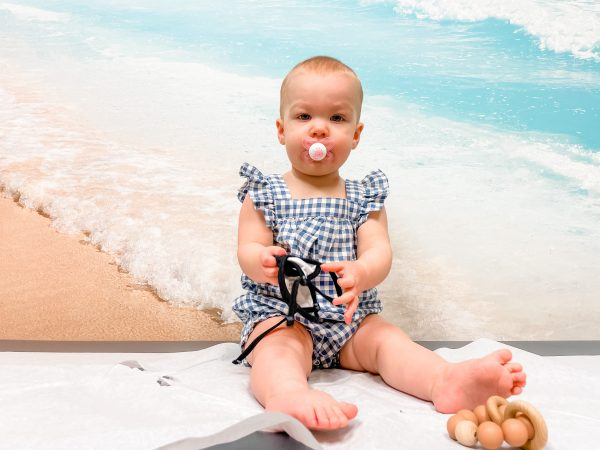 A baby posing in front of a beach background, made to look like the child is perched happily in the sand instead of on an exam table