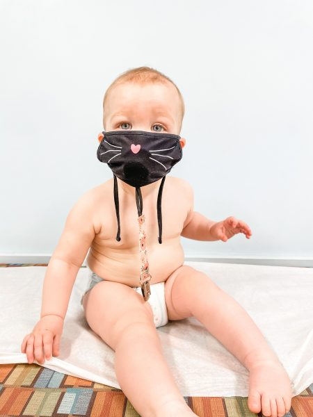 A diapered baby on an exam table with a black kitten face mask on